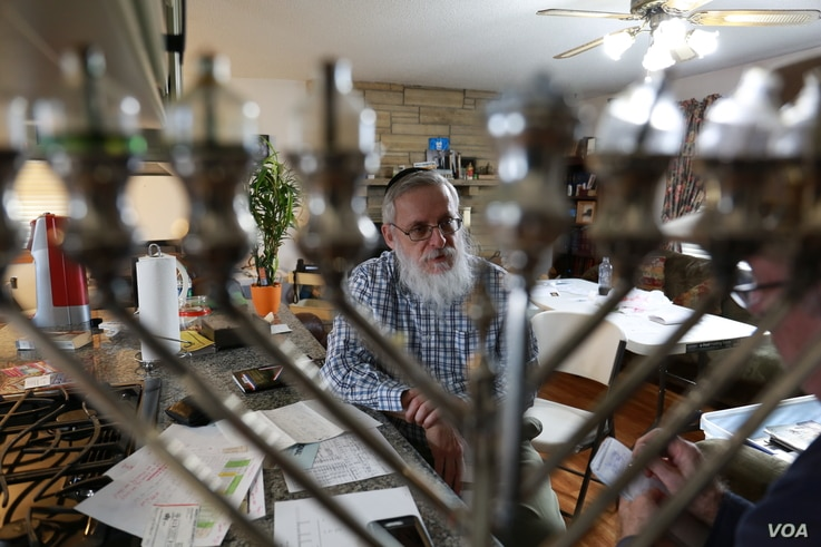 Seen through a menorah is Aaron Goldsmith, a Jewish community leader and business owner in Postville, Iowa. (Credit: Deepak Dophal)