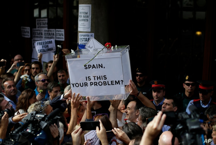 Pro-independence protestors hold up a fake ballot box as they gather outside the headquarters of the region's department of economic affairs in Barcelona, Spain, Sept. 20, 2017.