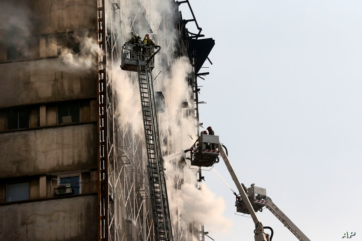 Iranian firefighters work to extinguish fire of the Plasco building before it collapsed, Jan. 19, 2017.