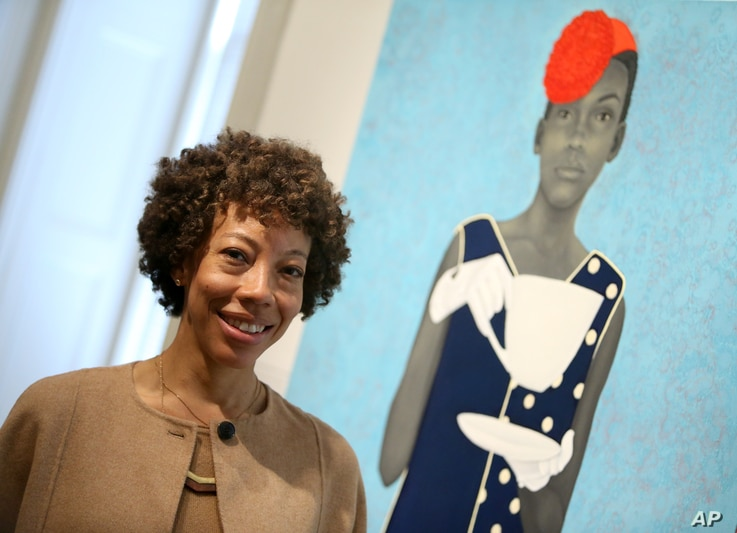 FILE - Amy Sherald, winner of the Outwin Boochever Portrait Competition 2016 first prize, stands in front of her work, March 11, 2016, at the Smithsonian's National Portrait Gallery in Washington D.C.
