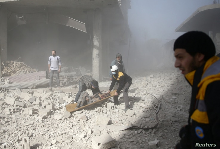 Civil defense members and civilians carry a wounded man in the town of Hamoria, Eastern Ghouta, near Damascus, Syria, Dec. 3, 2017.