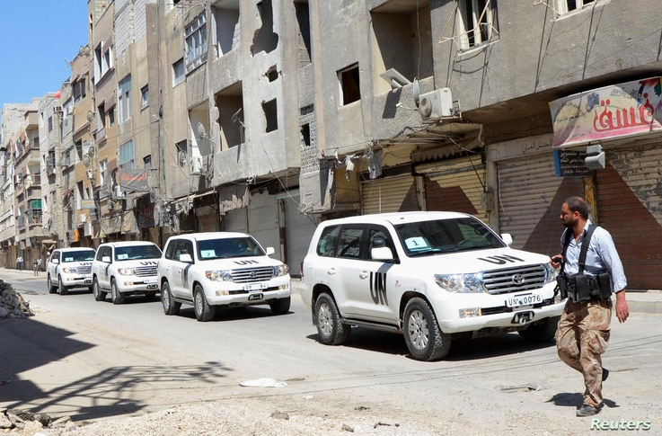 A Free Syrian Army fighter passes by the convoy of U.N. vehicles carrying a team of chemical weapons experts at the sites of an alleged chemical weapons attack in a Damascus suburb, August 28, 2013.
