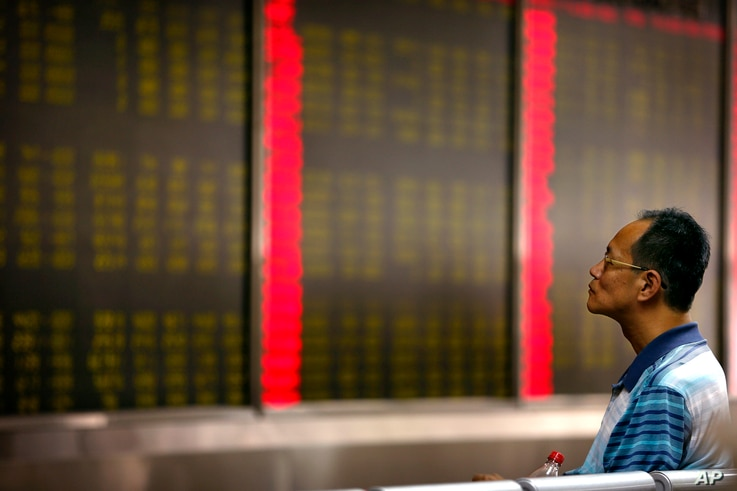 A Chinese investor monitors stock prices at  a brokerage house in Beijing, Aug. 24, 2015.