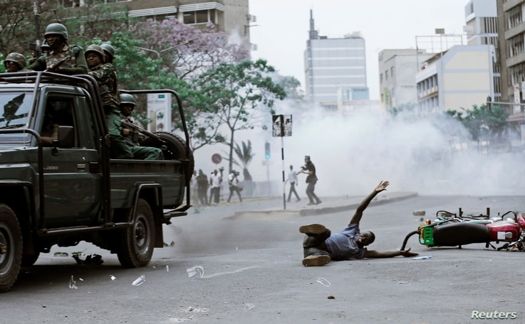 A supporter of Kenyan opposition National Super Alliance (NASA) coalition lies on the ground after he was hit by a police truck during a protest along a street in Nairobi, Kenya, Oct. 11, 2017.
