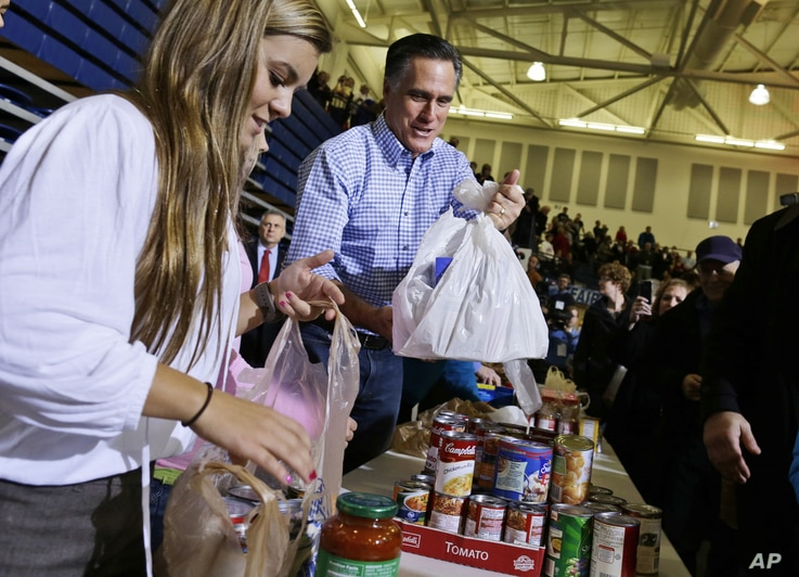 Republican presidential candidate Mitt Romney holds bags of food as he participates in a campaign event collecting supplies from residents local relief organizations for victims of superstorm Sandy in Kettering, Ohio, Tuesday, Oct. 30, 2012.