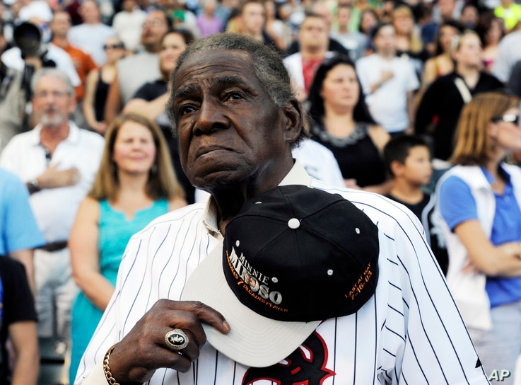 FILE - Former Negro Leaguer and Chicago White Sox player Minnie Minoso stands during the national anthem before a baseball game between the Chicago White Sox and the Texas Rangers, in Chicago, Aug. 24, 2013.
