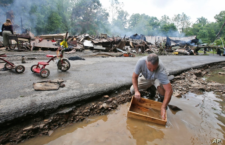 Mark Lester cleans out a box with creek water as he cleans up from severe flooding in White Sulphur Springs, W. Va., June 24, 2016. A deluge of 25 centimeters of rain on parts of West Virginia destroyed or damaged more than 100 homes.