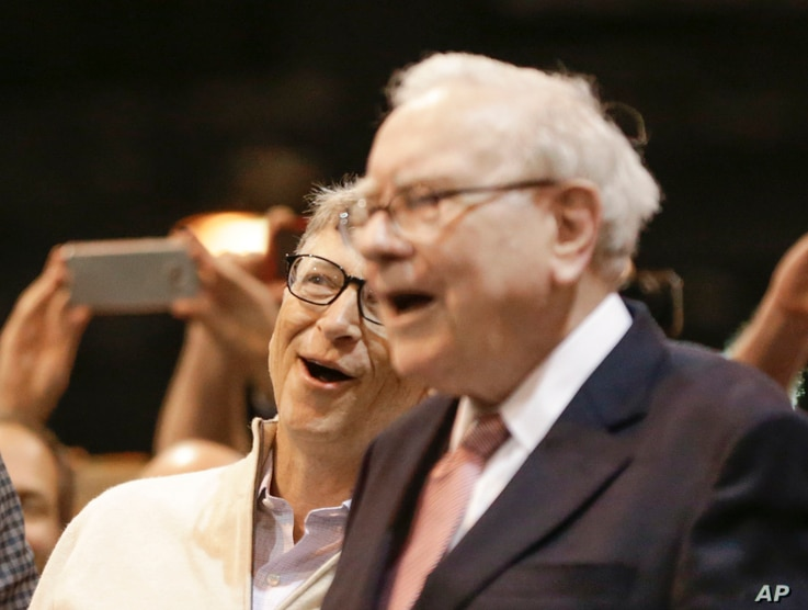 Berkshire Hathaway Chairman and CEO Warren Buffett and Berkshire Director Bill Gates (left) react to a successful throw during a newspaper tossing competition at the annual Berkshire Hathaway shareholders meeting at the CenturyLink Center in Omaha, N...