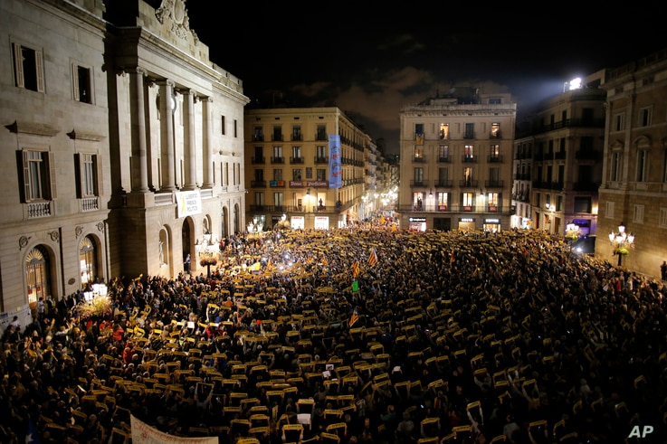 """Demonstrators holding banners reading in Catalan """"Freedom for the political prisoners"""" gather at the Barcelona town hall, during a protest against the decision of a judge to jail ex-members of the Catalan government, in Barcelona, Spain, Nov. 3, 2017..."""