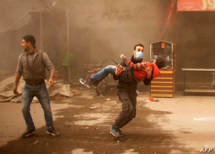 A member of the Syrian Civil Defence carries an injured child following regime air strikes on the rebel-held besieged town of Douma in the eastern Ghouta region, on the outskirts of the capital Damascus, on February 7, 2018.
