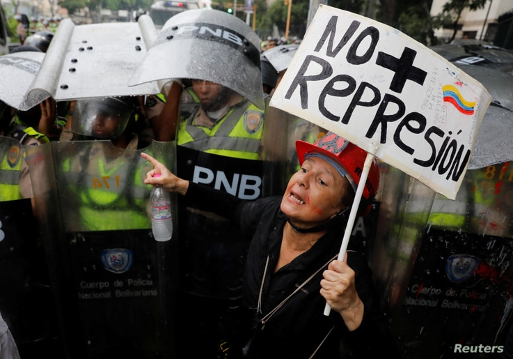 "An opposition supporter confronts riot security forces with a sign that reads ""No more repression"" during a rally against President Nicolas Maduro in Caracas, Venezuela, May 12, 2017."
