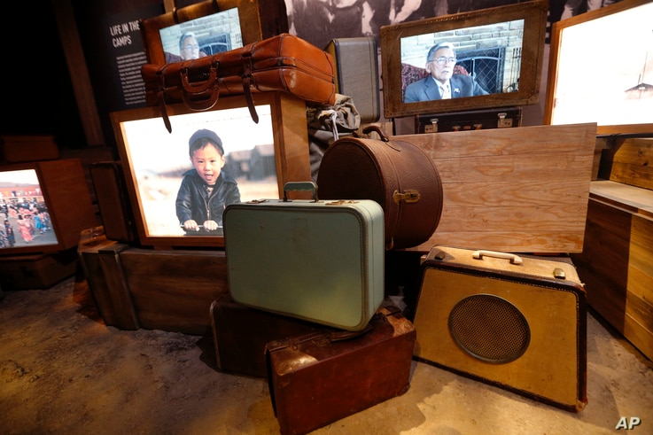 """Luggage, an image of a boy of Japanese descent, and a video interview of a man who was kept in an internment camp, are part of the permanent exhibit """"Salute to the Home Front"""" at the National World War II Museum."""