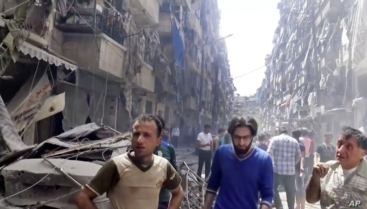 In this image made from video and posted online from Validated UGC, men look at damaged buildings after airstrikes hit Aleppo, Syria, April 28, 2016.