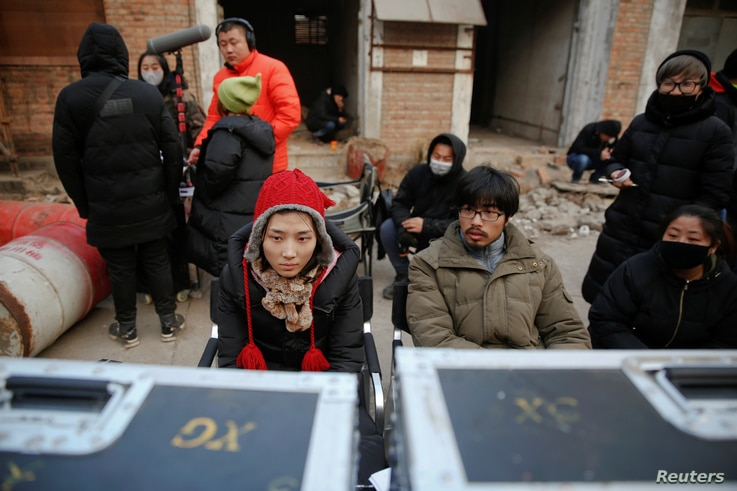 Director Shen Chenyan (second from right) and executive producer Liu Menghuan (left) watch a scene of their post-apocalyptic movie on the set in Langfang, Hebei province, China, Dec. 16, 2016.