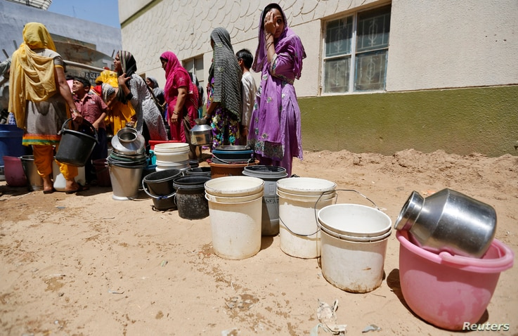 Residents wait for their turn to fill their containers with water, next to a municipal corporation water tanker in Maktampura neighborhood in Ahmedabad, April 7, 2016.
