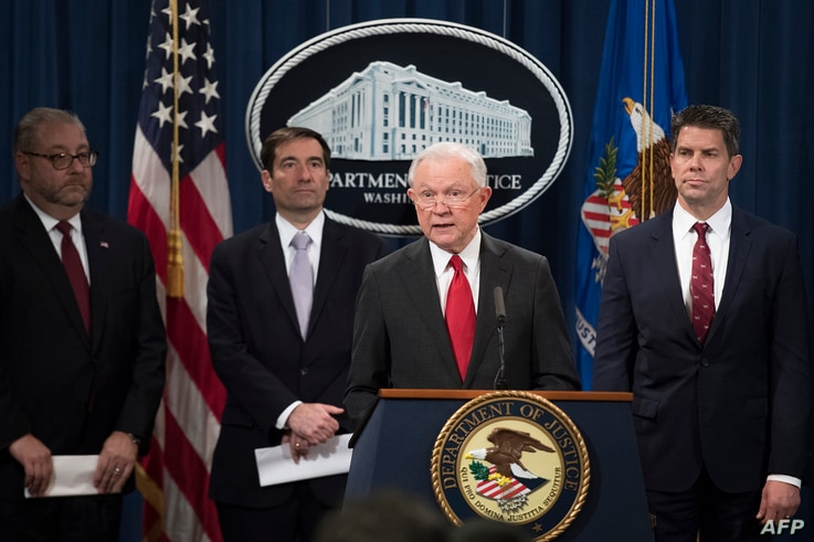 Attorney General Jeff Sessions, center, announces the creation of a new initiative to crack down on Chinese intelligence officials pilfering intellectual property from U.S. corporations during a press conference in Washington, Nov. 1, 2018.
