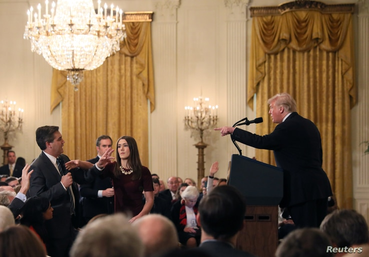 A White House staff member reaches for the microphone held by CNN's Jim Acosta as he questions U.S. President Donald Trump during a news conference following Tuesday's midterm U.S. congressional elections at the White House in Washington, U.S., Novem
