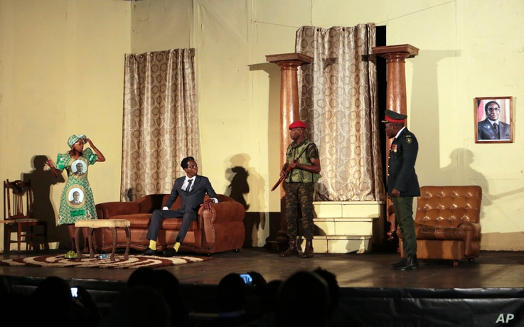 In this photo taken March, 28, 2018, actor Caroline Magenga, playing former Zimbabwean first lady Grace Mugabe, left, reacts as armed soldiers enter her house during a play dramatizing the events leading to Mugabe's resignation, in Harare, Zimbabwe.