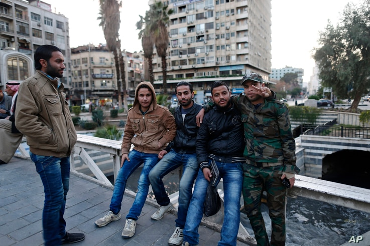 Syrian men pose for a picture as they gather in the Marjeh square in Damascus, Syria, Tuesday, Feb. 23, 2016. The Syrian government and the main umbrella for Syrian opposition and rebel groups announced on Tuesday they both conditionally accept a pro...