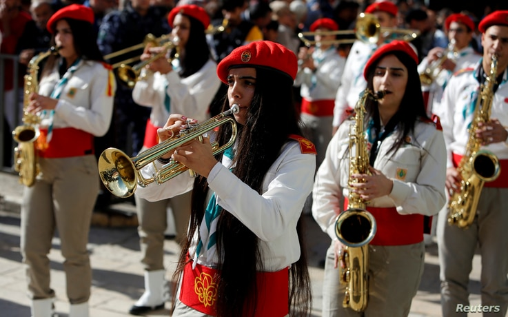 Members of a Palestinian marching band parade during Christmas celebrations at Manger Square outside the Church of the Nativity in Bethlehem, in the Israeli-occupied West Bank, Dec. 24, 2018.