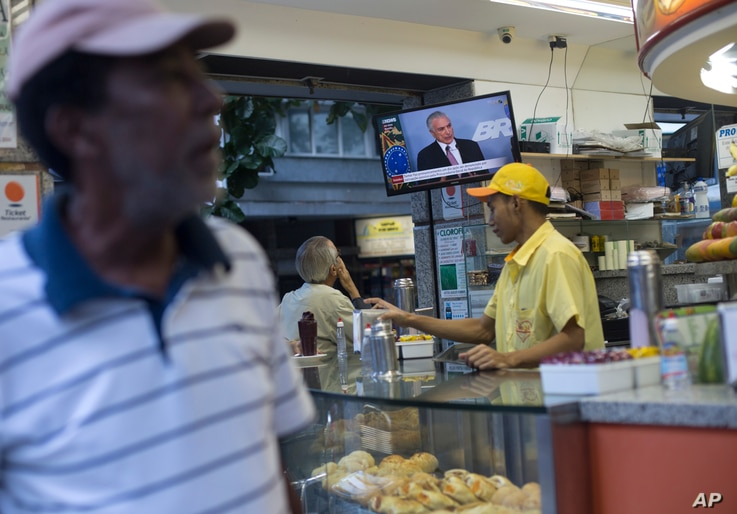 A customer watches a televised statement by Brazil's President Michel Temer at a snack bar in Rio de Janeiro, Brazil, June 27, 2017.
