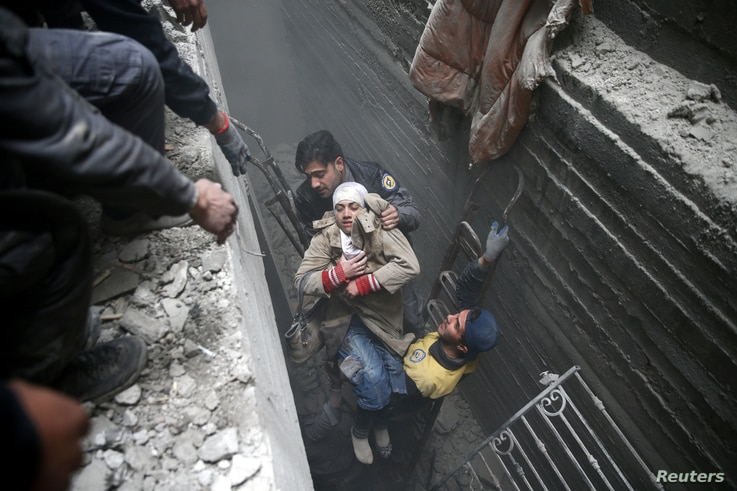 Syria civil defense workers help an unconscious woman from a shelter in the besieged town of Douma, eastern Ghouta, Damascus, Syria, Feb. 22, 2018.