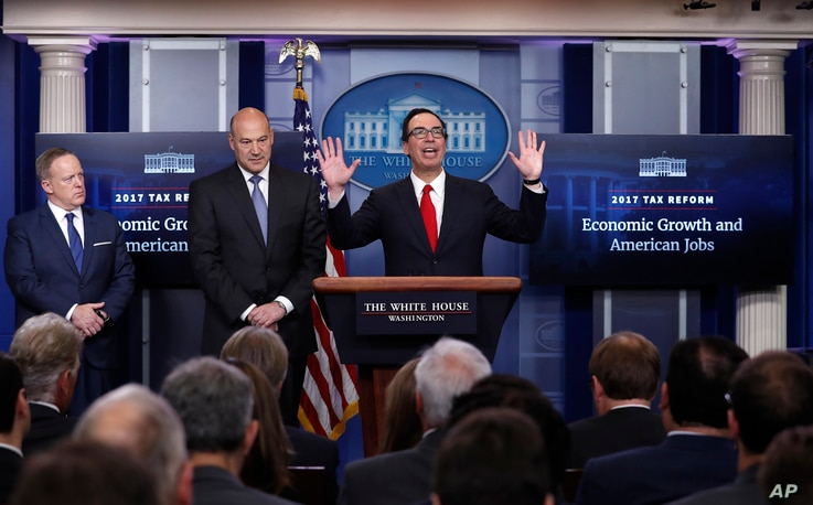 Treasury Secretary Steven Mnuchin, center, joined by National Economic Director Gary Cohn, center, and White House press secretary Sean Spicer speaks in the briefing room of the White House in Washington,  April 26, 2017.