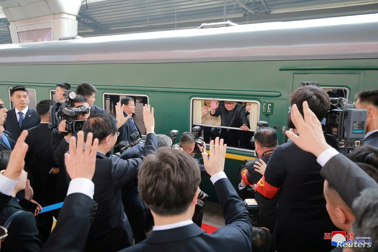 North Korean leader Kim Jong Un waves from a train, as he paid an unofficial visit to China, in this undated photo released by North Korea's Korean Central News Agency (KCNA) in Pyongyang, March 28, 2018.