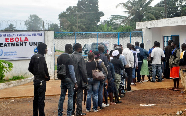 Liberian health workers queue to enter one of the largest Ebola treatment units at the Island Clinic Monrovia, Liberia. Oct. 13, 2014.