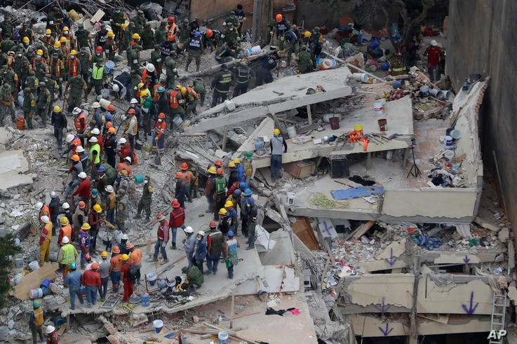 Rescue workers search for people trapped inside a collapsed building in the Del Valle area of Mexico City, Sept. 20, 2017.
