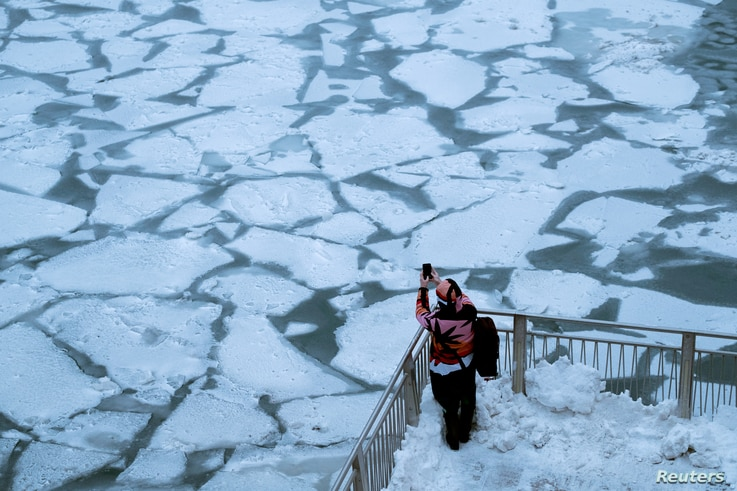 A pedestrian stops to take a photo by Chicago River, as bitter cold phenomenon called the polar vortex has descended on much of the central and eastern United States, in Chicago, Illinois, U.S., January 29, 2019.