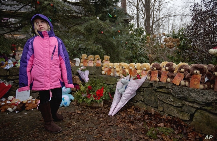 Ava Staiti, 7, of New Milford, Conn., looks up at her mother Emily Staiti, not pictured, while visiting a sidewalk memorial with 26 teddy bears, each representing a victim of the Sandy Hook Elementary School shooting, December 16, 2012, in Newtown, C...