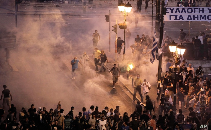 Demonstrators run away from tear gas during a demonstration in Athens on Tuesday June 28, 2011. A general strike disrupted services across Greece and riots erupted once more outside Parliament Tuesday as demonstrators protested more taxes and spendin...