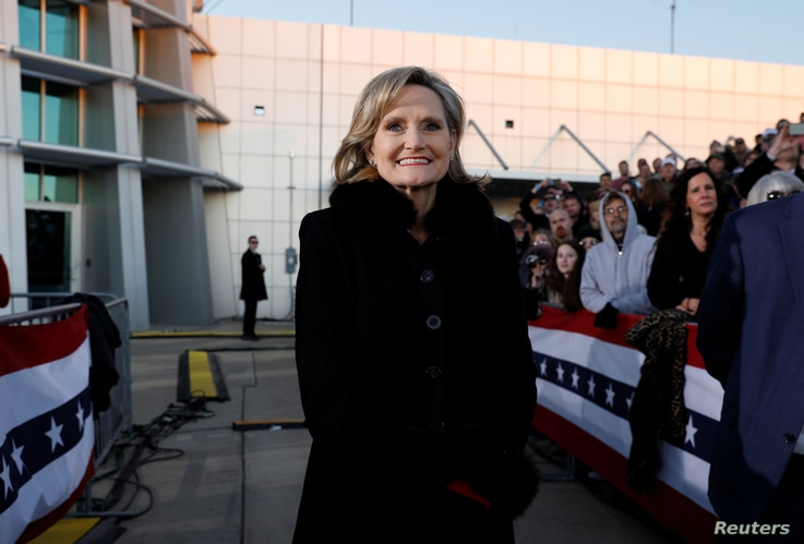 Republican U.S. Senator Cindy Hyde-Smith listens to U.S. President Donald Trump speak on her behalf during a Hyde-Smith campaign rally in Tupelo, Mississippi, Nov. 26, 2018.