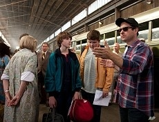 Center left to right: Joel Courtney (as Joe Lamb) and Riley Griffiths (as Charles) discuss a scene with director/writer/producer J.J. Abrams on the set of SUPER 8, from Paramount Pictures.