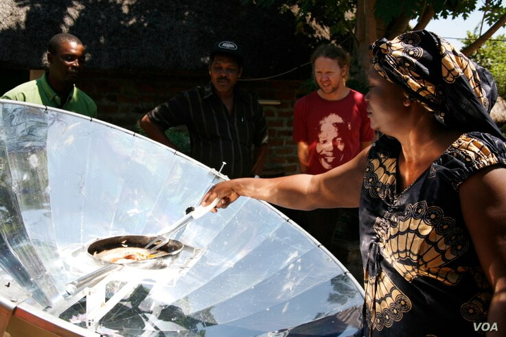 Solar energy champion Crosby Menzies watches a Zambian woman cooking on one of his unique cookers that are powered by the sun (Photo: Sunfire)