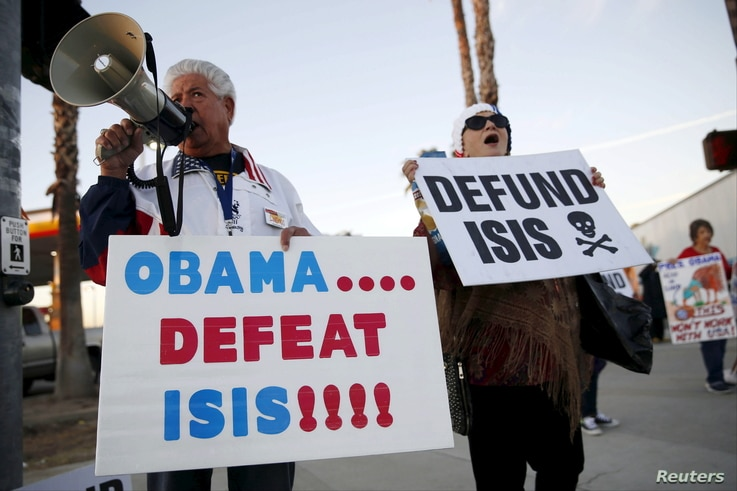 Raul Rodriguez Jr., left, of America First Latinos protests against the Islamic State group ahead of President Barack Obama's visit with the families of shooting victims in San Bernardino, Calif., Dec. 18, 2015.