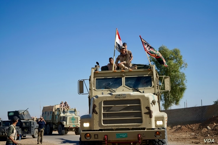 Iraqi troops move further into Mosul. Some army vehicles sported Shi'ite banners in addition to the Iraqi national flag, Nov. 3, 2016. (Photo: Jamie Dettmer for VOA)
