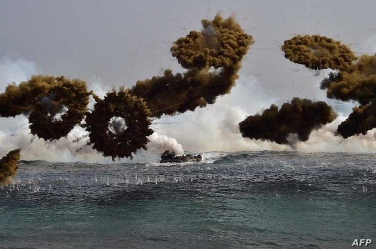 South Korean Marine amphibious assault vehicles fire smoke shells to land on the seashore during a joint landing operation by US and South Korean Marines in the southeastern port of Pohang on March 30, 2015. The drill is part of the annual joint exer...
