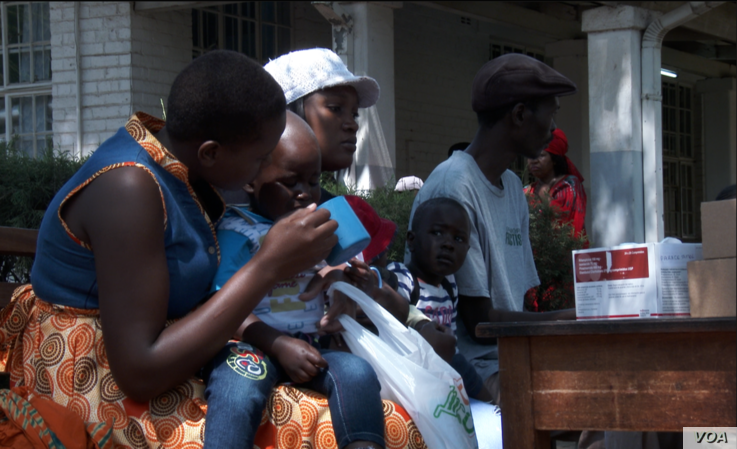 Officials force a child suspected of having contracting cholera to take an oral rehydrating solution at a temporary treatment center in Harare, Sept. 11, 2018. (C. Mavhunga/VOA)