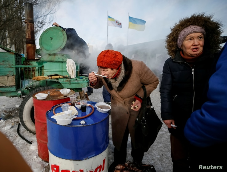 A local resident eats a meal at an emergency center after shelling hit supply infrastructure in the government-held industrial town of Avdiyivka, Ukraine, Feb. 1, 2017.