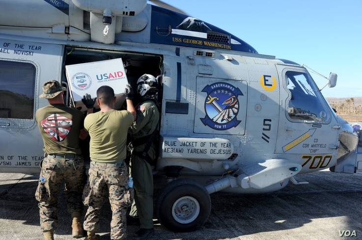 "U.S. Marines help load relief supplies onto an MH-60R Seahawk from the ""Saberhawks"" of Helicopter Maritime Strike Squadron (HSM) 77 to be airlifted to remote areas in support of Operation Damayan. (US Navy)"