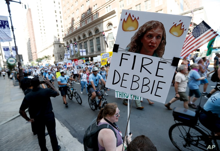 A supporters of Sen. Bernie Sanders, I-Vt., holds up a sign call calling for Debbie Wasserman Schultz, chairwoman of the Democratic National Committee to be fired, Sunday, July 24, 2016, in Philadelphia.