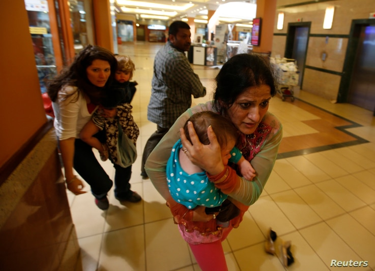 Women carrying children run for safety as armed police hunt for gunmen who went on a shooting spree in Westgate shopping center in Nairobi September 21, 2013.