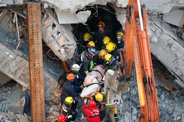 Emergency rescuers remove a body found in a collapsed building from an earthquake in Tainan, Taiwan, Feb. 7, 2016.