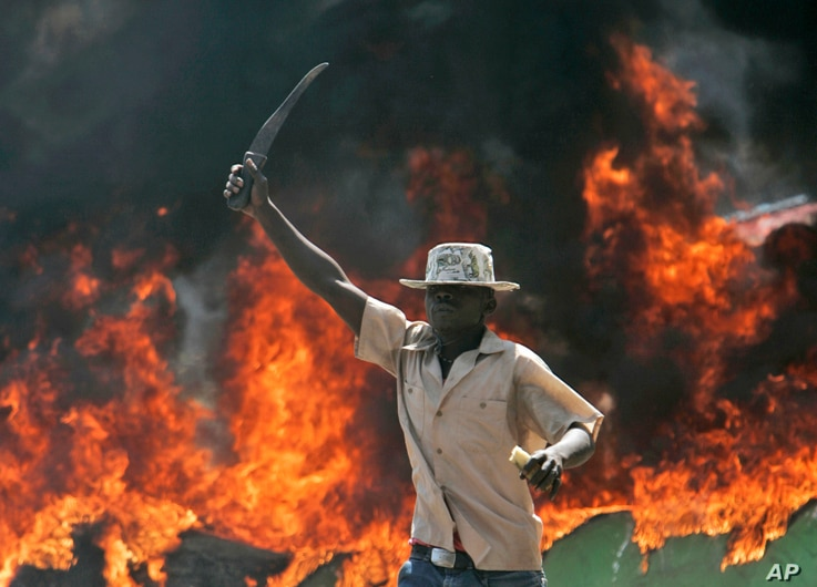 A supporter of the Orange Democratic Party hold up a machete in front of a burning baricade during riots in the Kibera slum in Nairobi, (File photo).