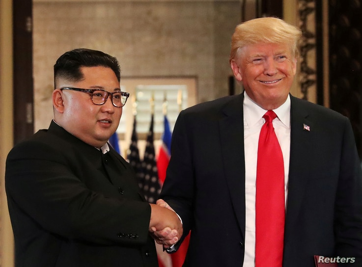 FILE - U.S. President Donald Trump and North Korean leader Kim Jong Un shake hands after signing documents during a summit at the Capella Hotel on the resort island of Sentosa, Singapore, June 12, 2018.