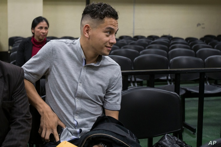 Jose Manuel Morales Marroquin, the son of Guatemala's President Jimmy Morales, center, sits in a courtroom waiting for a hearing in Guatemala City, Aug. 30, 2017.