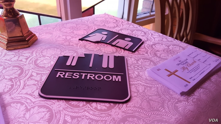 A broken restroom sign in the foyer at Wedgewood Church in Charlotte, North Carolina. (W. Gallo/VOA)
