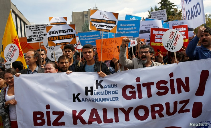 """FILE - Demonstrators hold signs in front of the High Education Board during a protest against the suspension of academics from universities following a post-coup emergency decree, in Ankara, Turkey, Sept. 22, 2016. The sign in the foreground reads """"L..."""